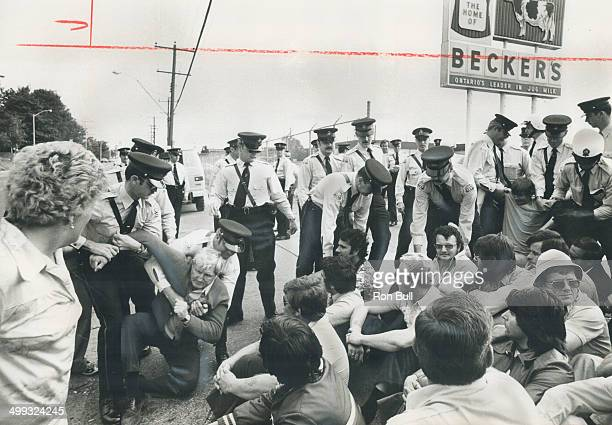 Policemen start to remove; some of the pickets who sat on the roadway this morning trying to block across to the Becker's milk plant on Warden Ave....
