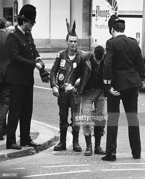 Policemen stop a couple of young punks in the street during the 'Stop the City' anarchist demonstration in London September 1984