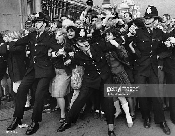 Policemen struggle to restrain young Beatles fans outside Buckingham Palace as The Beatles receive their MBEs in 1965 John Lennon later returned his...
