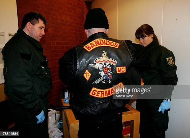 Policemen surround a member of the biker group 'Bandidos' outside the district court on January 9,2008 in Muenster, Germany. The two biker groups at...