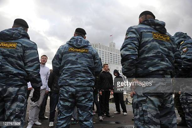 Policemen surround Russian nationalist movement supporters near the Government building during a rally devoted to remembrance of people killed by...