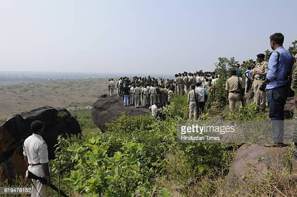 Policemen surround the area where eight SIMI terrorist were killed in an encounter lying on ground at Acharpura on October 31 2016 in Bhopal India...