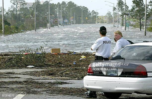 Policemen survey a road flooded in the aftermath of Hurricane Ivan in Gulf Shores, 16 September 2004. At least 14 peope died as Hurricane Ivan slamed...