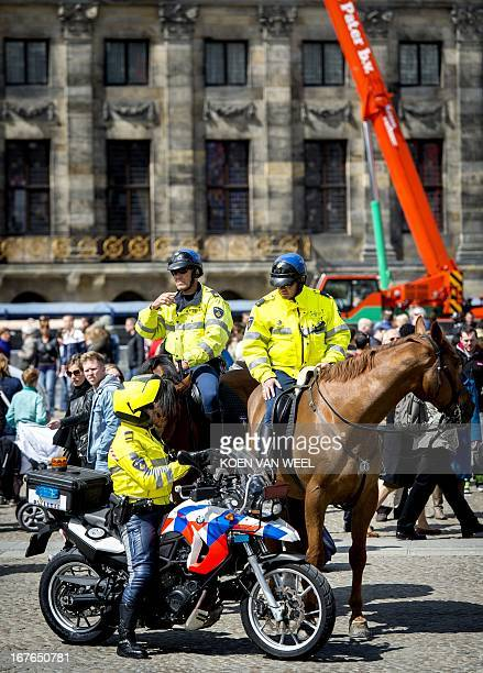Policemen survey a street in the center of Amsterdam The Netherlands on April 27 2013 during the preparations for the abdication of Dutch Queen...