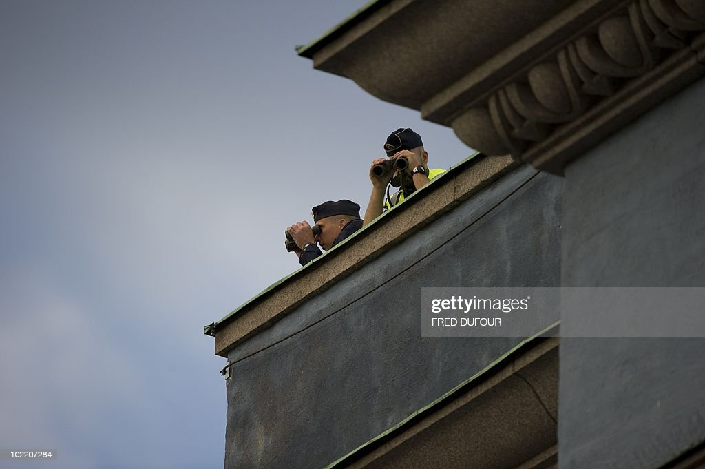 Policemen survey the crowds from a rooftop as guests arrive for a gala performance at the Stockholm Concert Hall in Stockholm on June 18, 2010, at the start of the weekend's wedding celebrations. Less than half Sweden's population now supports the monarchy, and a quarter thinks it a bad thing, a poll showed today amid preparations for Crown Princess Victoria's nuptials this weekend.