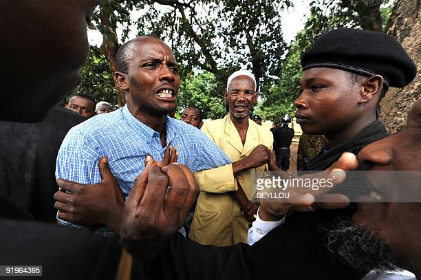Policemen try to contain relatives reacting as they stand on October 2 2009 in front of the Conakry great mosque where several dozen bodies of...