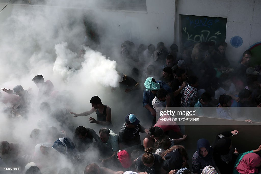 Policemen try to disperse hundreds of migrants by spraying them with fire extinguishers during a gathering for a registration procedure at the stadium on the Greek island of Kos, on August 11, 2015. Police on the Greek island on Kos hit migrants with truncheons to prevent a stampede, a day after an officer was caught on camera slapping a migrant. The incident occurred as hundreds of migrants were being relocated to a local football stadium, after camping alongside roads and beaches across the island for weeks. / AFP / ANGELOS