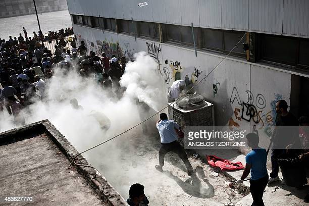 Policemen try to disperse hundreds of migrants by spraying them with fire extinguishers during a gathering for a registration procedure at the...