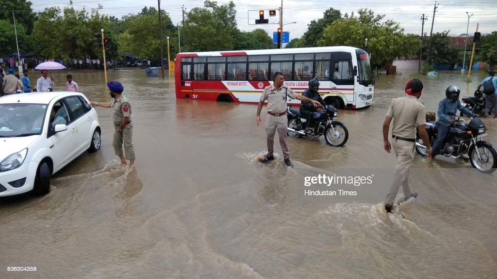 Policemen try to manage traffic due to waterlogging in sector 44-50 dividing after the heavy rain on August 21, 2017 in Chandigarh, India. Heavy rainfall on morning brought the tri-city (Chandigarh, Mohali, Panchkula) to a stand still as poor drainage system gave way to roads being flooded with water. The rainfall left the cars of commuters stuck in middle of the roads forcing them to leave their cars stranded.