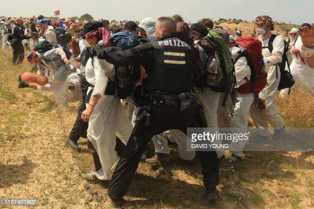 Policemen try to prevent climate activists from entering the grounds of the Garzweiler brown coal mine in Garzweiler, western Germany, on June 22...