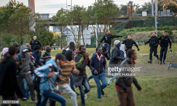 Policemen try to prevent migrants from reaching the Channel Tunnel in Coquelles near Calais northern France on late July 29 2015 One man died...
