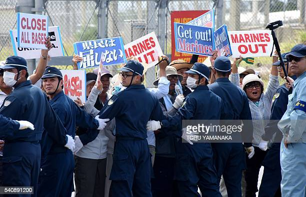 Policemen try to remove people protesting against the presence of US bases in front of the gate of the US Marine Corps' Camp Schwab in Nago on the...