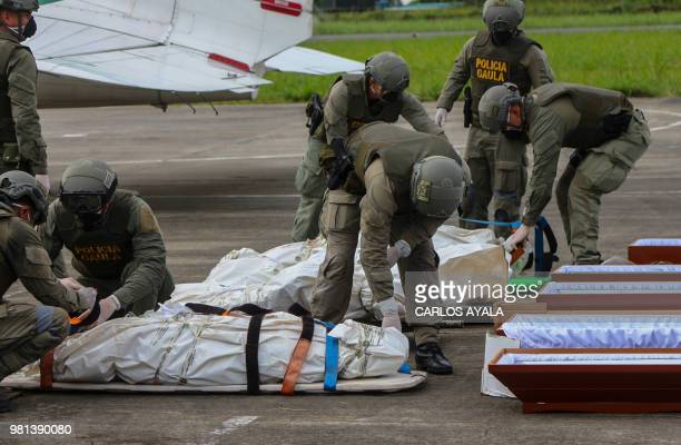 Policemen unload corpses allegedly belonging to the press team of Ecuadorean newspaper El Comercio from a helicopter in Tumaco Colombia on June 22 to...