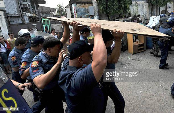 Policemen use plywood to shield themselves as they chase local residents after they threw rocks at a demolition crew during the demolition of shanty...