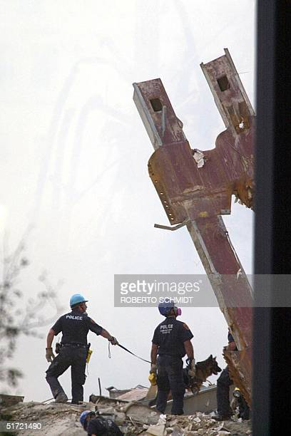Policemen use rescue a dog 16 September 2001 at the World Trade Center in New York Rescue and recovery efforts continue after the twin towers were...