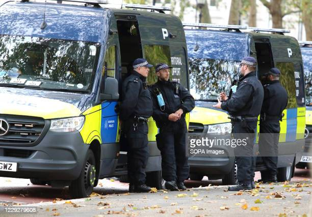 Policemen wait outside their Territorial Support Unit vans as they await a call to action. With a number of expected demonstrations taking place in...