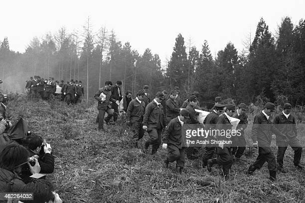 Policemen walk down the mountain carrying the bodies of the lynch victims of the United Red Army 's internal dispute after a confession was made by...