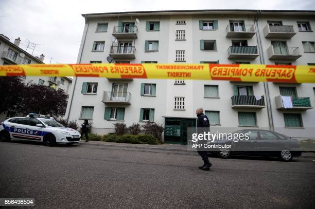 Policemen walk in a security perimeter set near a building where a fire broke out overnight killing five people in Mulhouse on October 2 2017 / AFP...