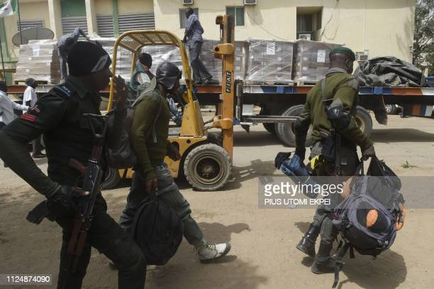 Policemen walk past electoral materials being offloaded at the headquarters of Independent National Electoral Commission in Kano Nigeria on February...