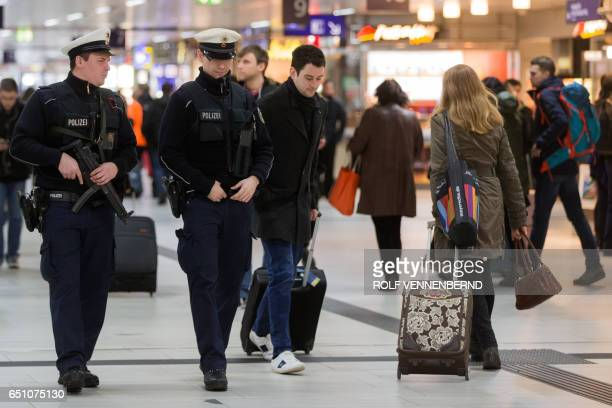 Policemen walk past passengers on March 10 2017 in the main train station of Duesseldorf western Germany one day after German police have arrested an...