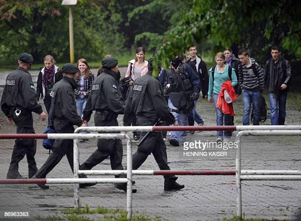 Policemen walk past pupils leaving their AlbertEinstein grammar school in Sankt Augustin near Bonn western Germany on May 11 2009 German police...