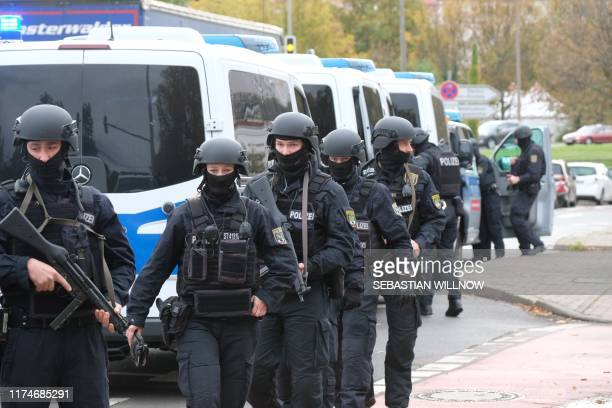 Policemen walk through a street close to the site of a shooting in Halle an der Saale eastern Germany on October 9 2019 At least two people were...