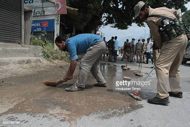 Policemen wash the blood stains after two policemen were killed by suspected militants in a shootout in Zadibal in the old part of the city on May 23...
