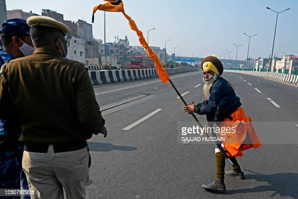 Policemen watch as a farmer takes part in a rally as farmers continue to protest against the central government's recent agricultural reforms in New...