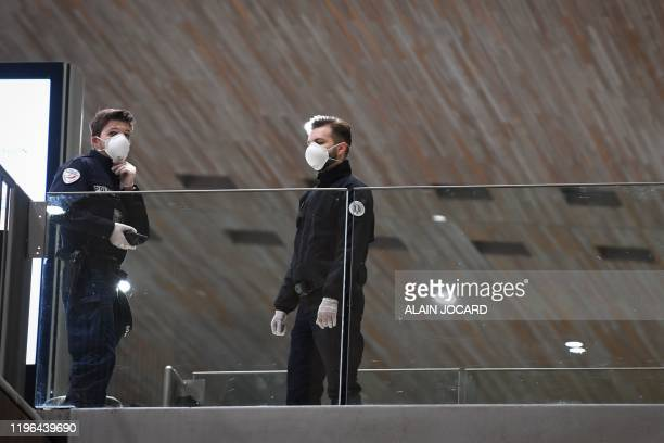 Policemen wear protective face masks as they stand in a arrival Terminal in Charles De Gaulle Airport, in Roissy on January 26, 2020 in...