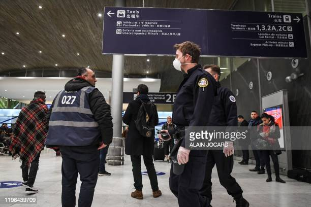 Policemen wearing protective face masks patrol at the arrival Terminal in Charles De Gaulle Airport, in Roissy-en-France on January 26, 2020. - China...