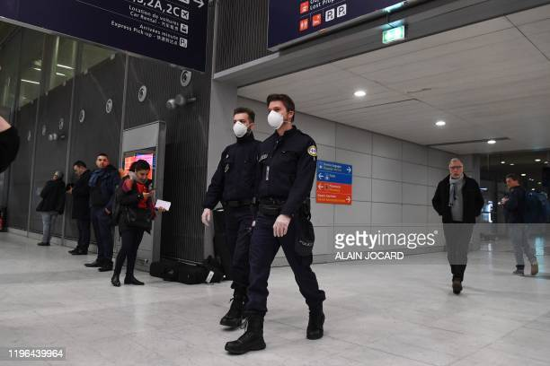 Policemen wearing protective face masks patrol in the arrival Terminal in Charles De Gaulle Airport on January 26, 2020 in Roissy-en-France. - China...