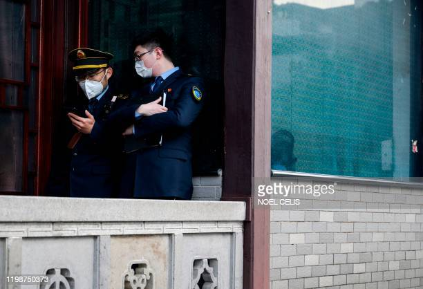 Policemen wearing protective facemasks use a mobile phones along a street in Hangzhou some 175 kilometres southwest of Shanghai on February 5 2020...