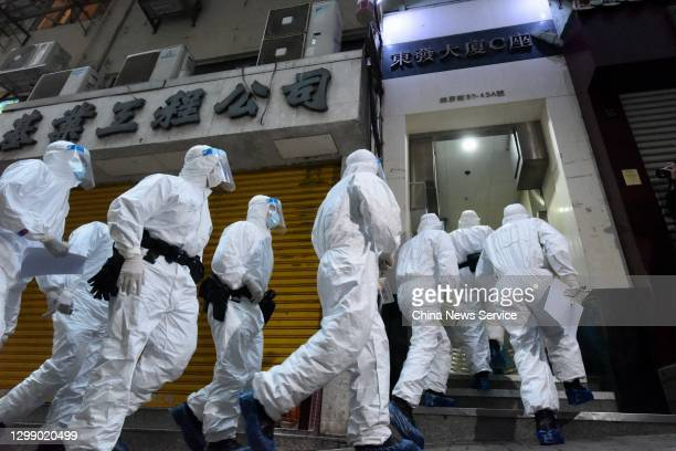 Policemen wearing protective suits transfer residents living at Tung Fat Building in North Point on January 27, 2021 in Hong Kong, China.