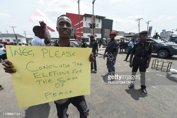Policement stand as a protester holds a placard reading 'Please conclude the elections for the sake of peace' during a demonstration against the...