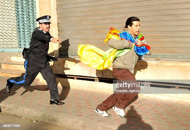 A polices officer chases a member of Berber people as Berber people stage a demonstration in the memory of people who lost their lives during the...