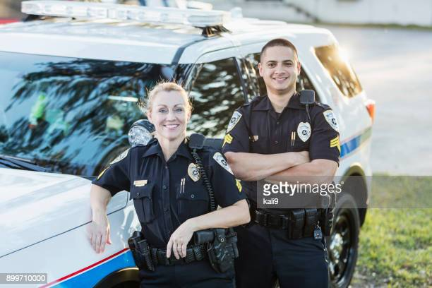 policewoman and partner next to squad car - forze di polizia foto e immagini stock