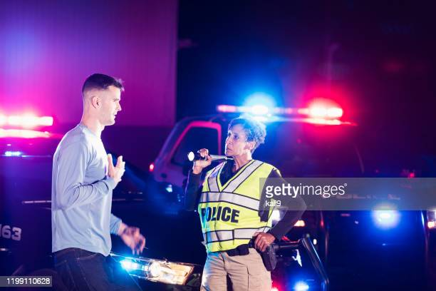 policewoman at night talking with young man - witness stock pictures, royalty-free photos & images