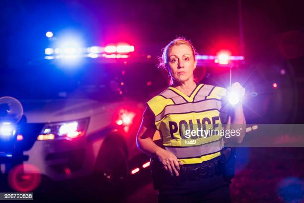 Policewoman at night with flashlight, emergency lights