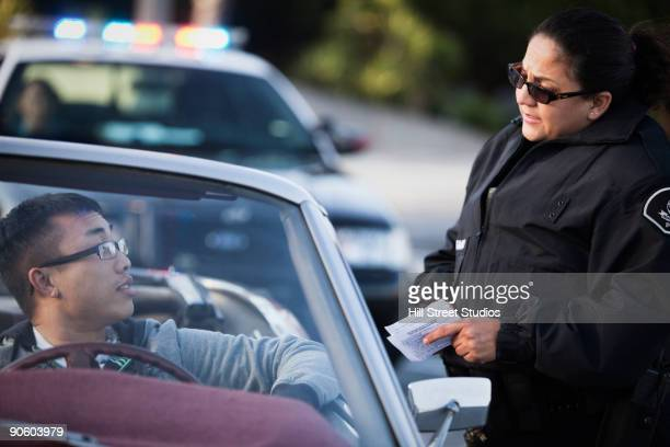 Policewoman checking paperwork of man in convertible