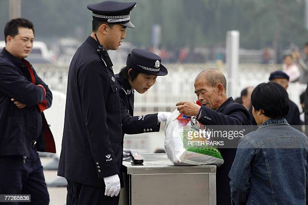 Policewoman checks a man's bag on Tiananmen Square in Beijing, 11 October 2007, as China's ruling Communist Party has intensified a crackdown on...