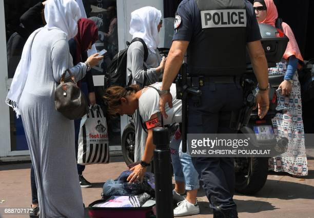 A policewoman checks a suitcase after police officers arrested veiled women on May 26 2017 outside the luxury Martinez hotel before they attempted...