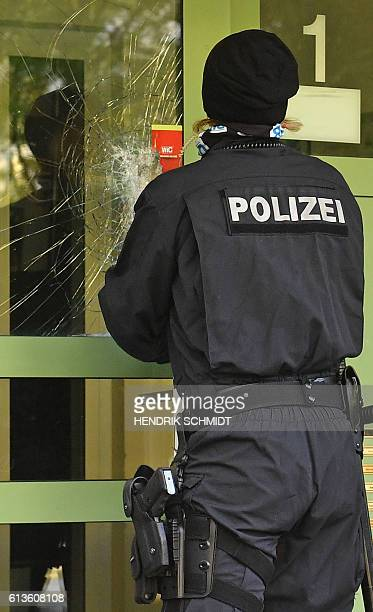 A policewoman closes the broken door of an apartment building at the Yorckgebiet district of Chemnitz eastern Germany where German police commandos...