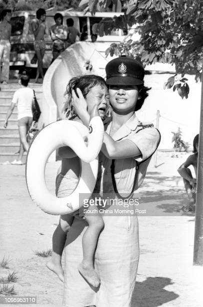 A policewoman comforting a crying bather in Repulse Bay 08MAY77