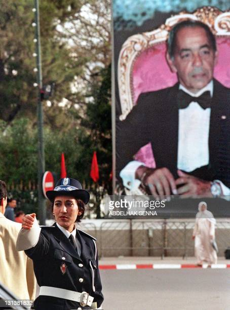 A policewoman controls the traffic on Mohamed V avenue under a huge portrait of Morocco King Hassan II on the 37th anniversary of Hassan II's...