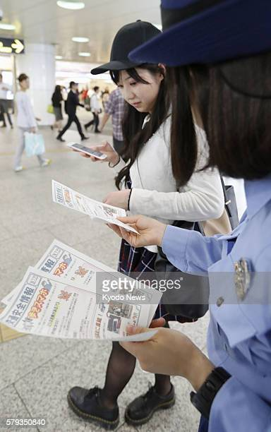 A policewoman distributes flyers near busy Shinjuku Station in Tokyo on July 22 calling on people not to play the Pokemon Go mobile game while...