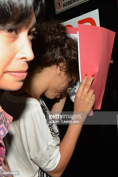 A policewoman escorts Heather Mack suspected in the murder of her mother Sheila von Wiese Mack while in custody at Bali police hospital in Denpasar...