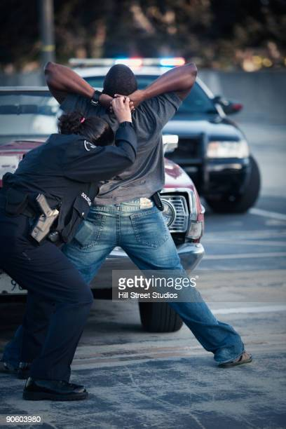 policewoman frisking man - restraining stock photos and pictures