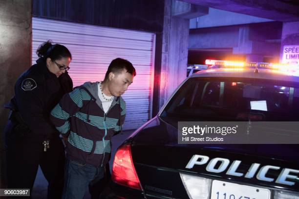 policewoman handcuffing man - arrest stock pictures, royalty-free photos & images