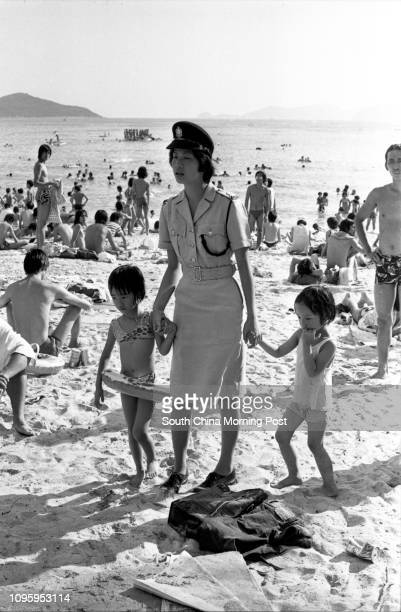 A policewoman holding hands of little bathers in Repulse Bay where a promotional campaign for police recruitment is being held 08MAY77