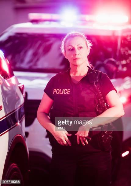 Policewoman in bulletproof vest by police cars